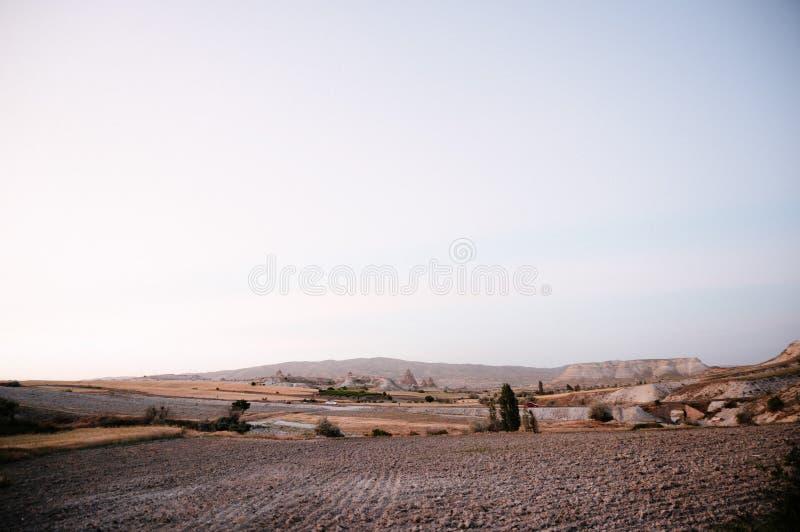 Rocks som ser som champinjoner t?nde dramatiskt, vid en solnedg?ng i Cappadocia, Turkiet royaltyfri bild