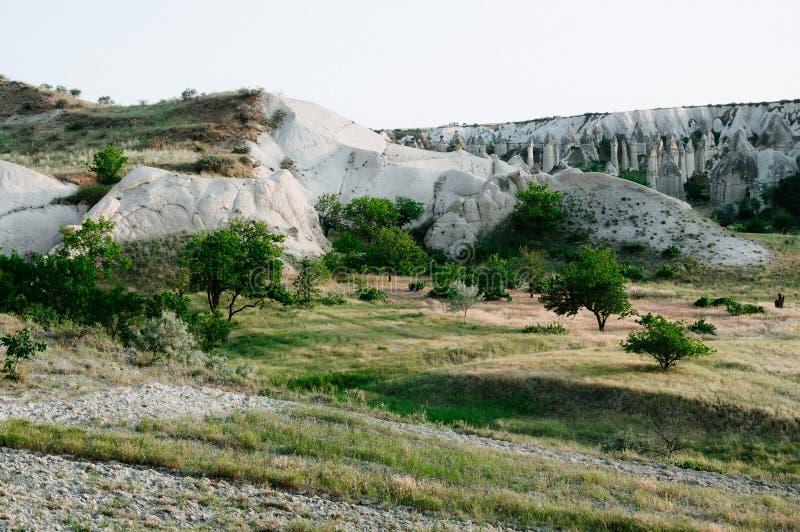 Rocks som ser som champinjoner t?nde dramatiskt, vid en solnedg?ng i Cappadocia, Turkiet arkivbilder