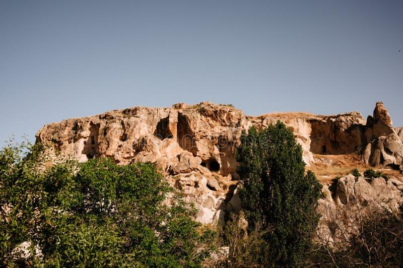 Rocks som ser som champinjoner t?nde dramatiskt, vid en solnedg?ng i Cappadocia, Turkiet royaltyfri foto