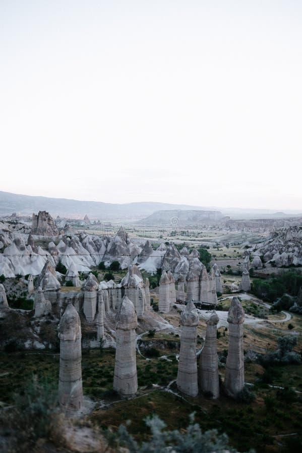 Rocks som ser som champinjoner t?nde dramatiskt, vid en solnedg?ng i Cappadocia, Turkiet royaltyfri fotografi