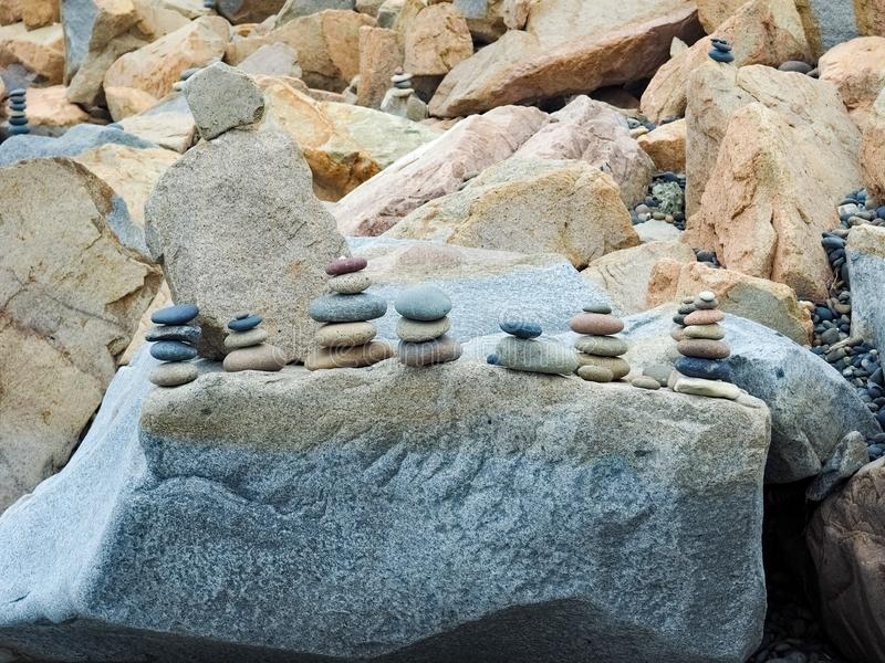 Rocks Stacked on Beachside Boulders. Stones and rocks of a variety of colors stacked on boulders on the beach near San Diego, California stock photo