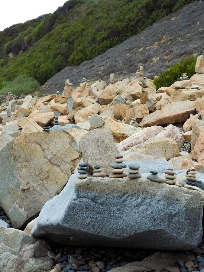 Rocks Stacked on Beachside Boulders. Stones and rocks of a variety of colors stacked on boulders on the beach near San Diego, California stock images