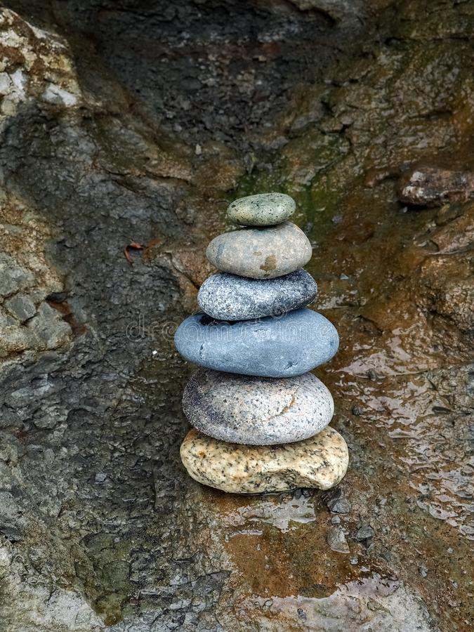 Rocks Stacked in a Beachside Cave. Stones and rocks of a variety of colors stacked in a cave on the beach near San Diego, California royalty free stock images