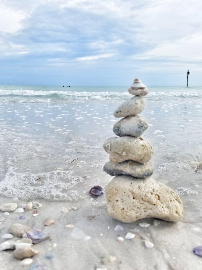 Rocks staplade nära vattnet på stranden arkivbild
