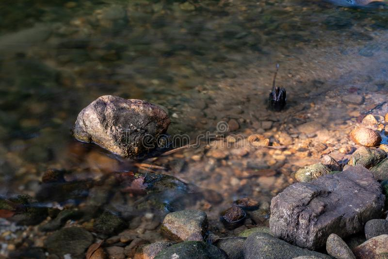 Rocks in stream with smooth flowing water stock photography
