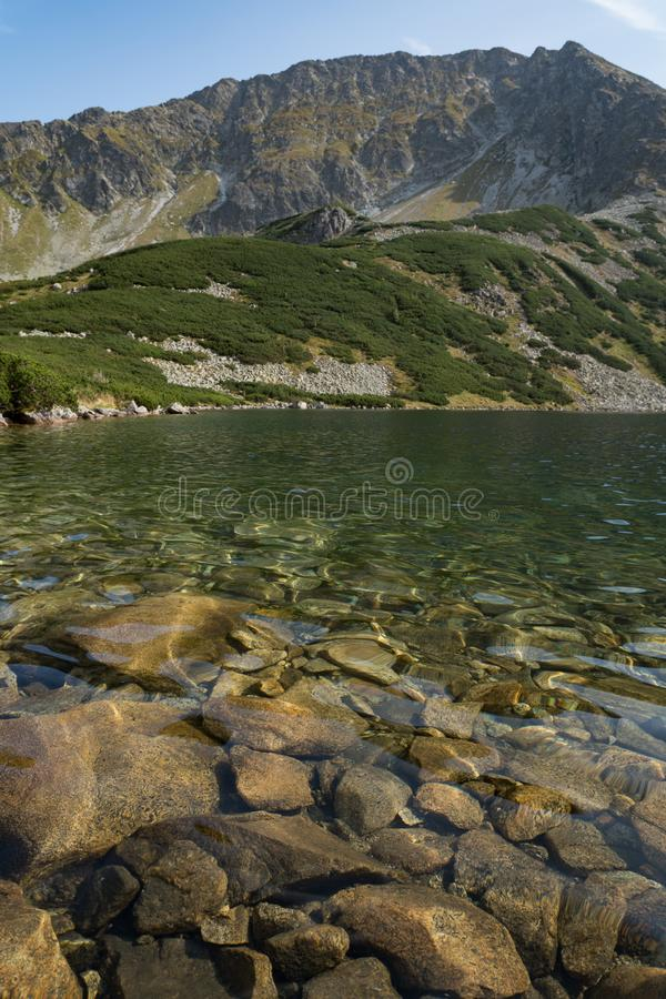 Rocks under water and mountain in Five Polish Ponds Valley stock photos