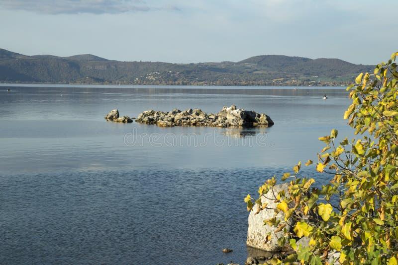 Bracciano`s lake, view from Anguillara Sabazia. Rocks and vegetation in Bracciano`s lake, view from Anguillara Sabazia, province of Rome, Lazio, Italy royalty free stock photos