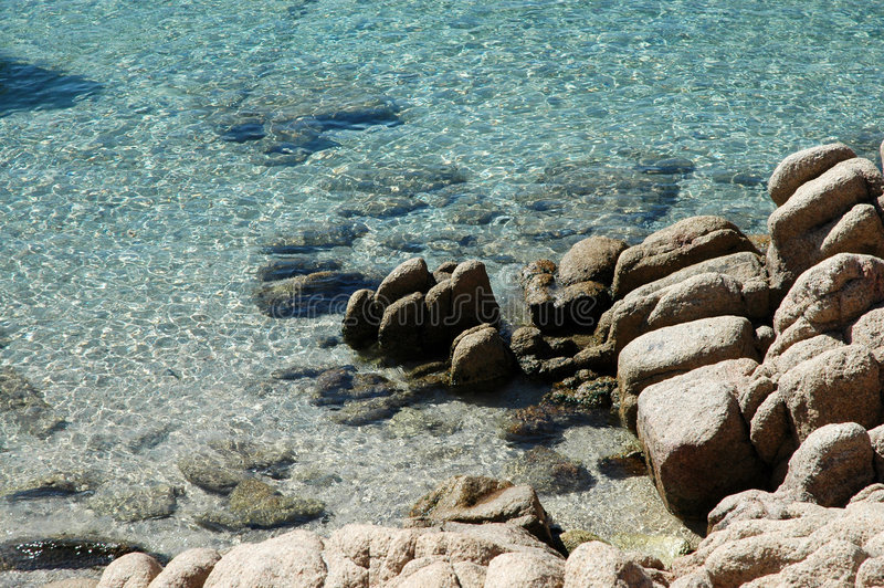 Rocks and water. Rocks in trasparent and blue water of the sea stock photography