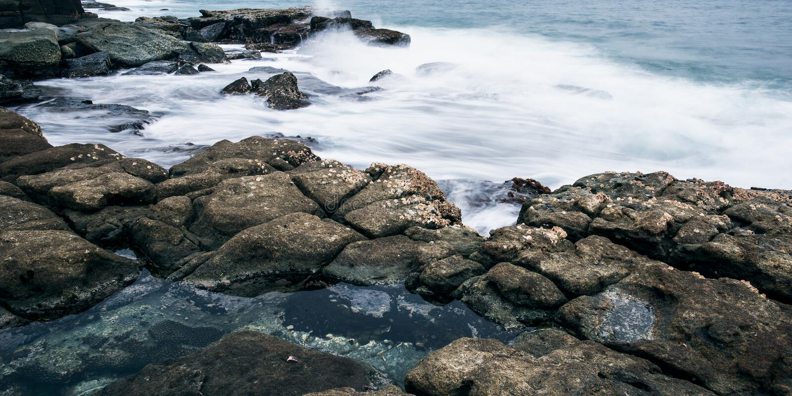 Rocks and waves at Point Cartwright stock photography