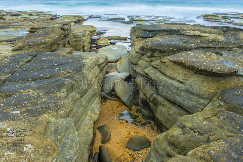 Rocks and waves at Point Cartwright stock images
