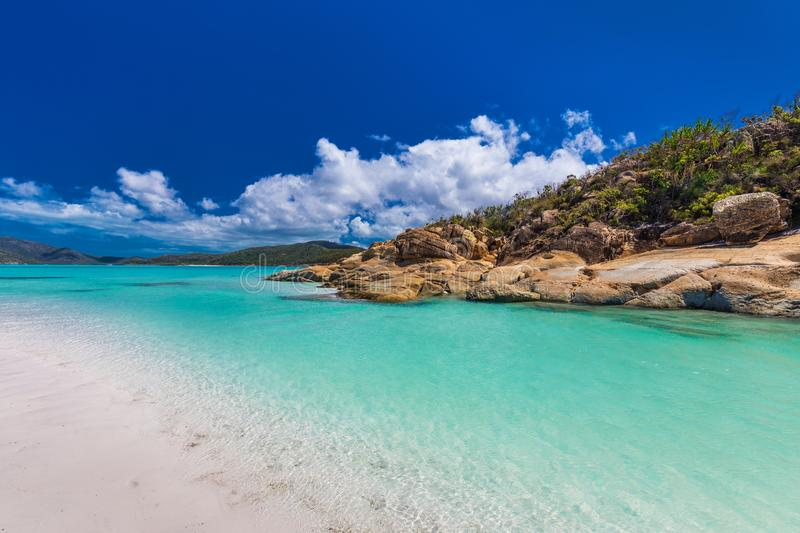 Rocks on Whitehaven Beach with white sand in the Whitsunday Islands, Queensland, Australia. Rocks on amazing Whitehaven Beach with white sand in the Whitsunday royalty free stock image