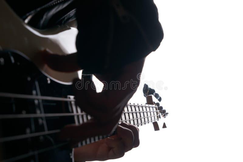 Rockstar en la chaqueta de cuero del motorista que juega a solas en la guitarra baja foto de archivo