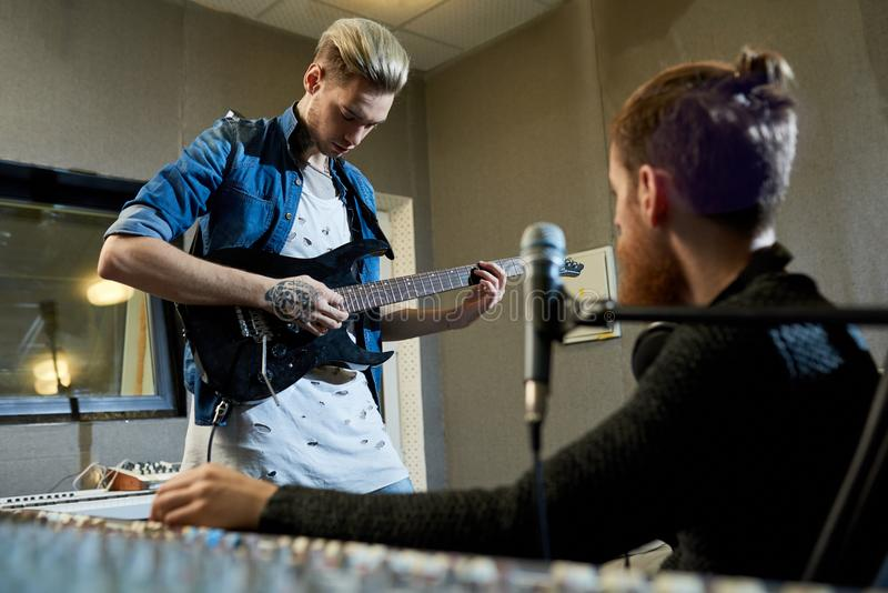 Rockstar gitarzysta komponuje nową piosenkę z producentem obraz stock
