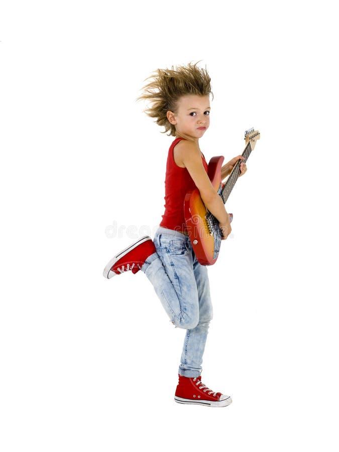 Rockstar kid dances with guitar. Rockstar kid dances with electric guitar stock photo