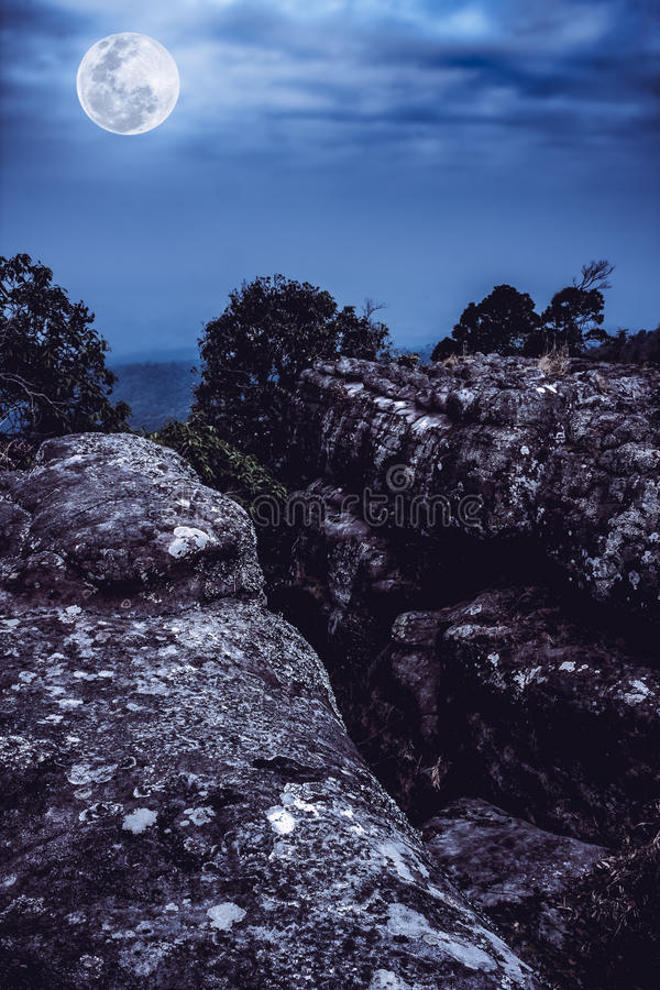 Rocky against blue sky and beautiful full moon at night. Outdoor royalty free stock photos