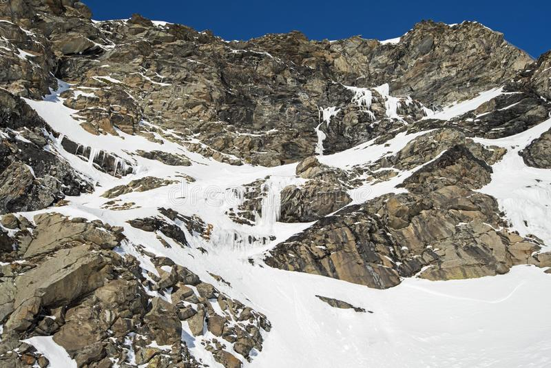 Rocky alpine mountainside with frozen waterfall. Rugged alpine rocky mountainside with frozen waterfall covered in snow and ice stock photos