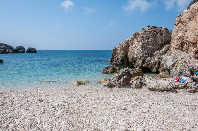 Rocky bay. Beach scene by the Greece again sea, with golden sand leading to the deep blue water stock photography