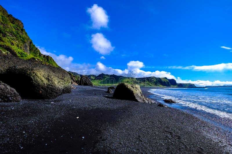 Rocky beach against green cliffs royalty free stock photos