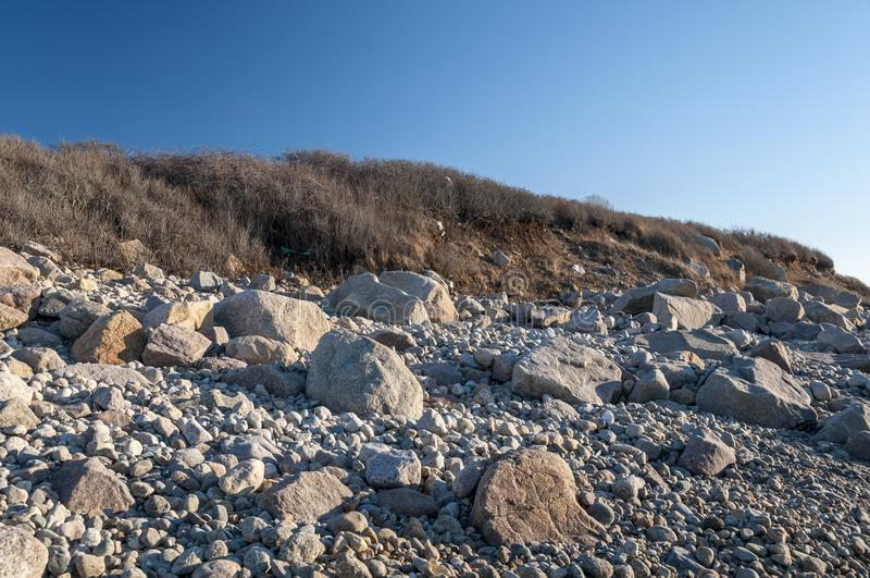 Rocky beach along Buzzards Bay. Steep, rock-strewn shoreline in late afternoon sun at Gooseberry Neck in Westport, Massachusetts royalty free stock image