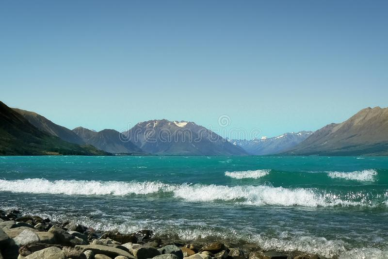 Waves crashing on rocky shore at Lake Ohua, South Island, New Zealand. Rocky beach and beautiful view over Lake Ohua, South Island, New Zealand royalty free stock photography