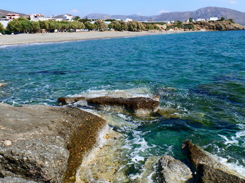 Rocky Beach. Beach in Crete, Greece, with blue, clear water and white houses stock photo