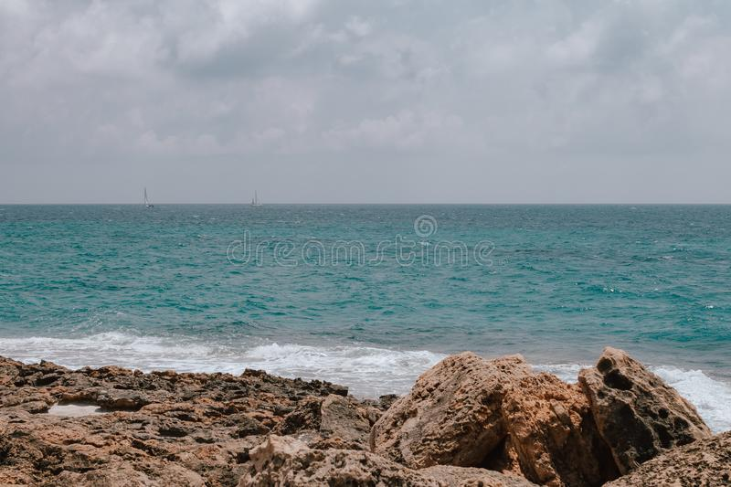 Rocky beach in Mallorca, in summer at high tide with the waves hitting and breaking on the coast.Rocky beach in Mallorca. Rocky beach in Mallorca, in summer at stock images