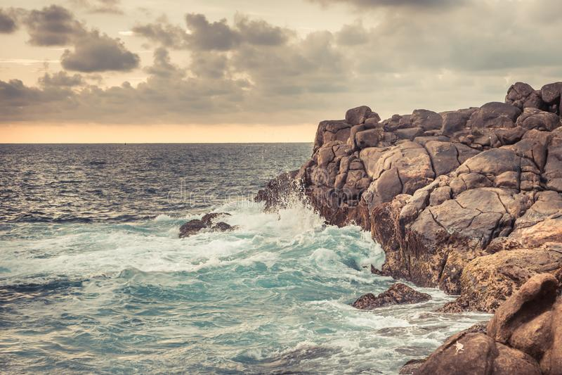 Rocky beach with stormy ocean and sunset sky as tropical landscape in Sri Lanka stock photography