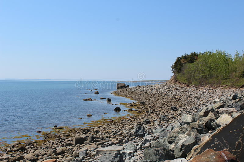 A rocky beach on a summer day on Cape Breton Island. A rocky shore on Cape Breton Island, Nova Scotia Canada stock images