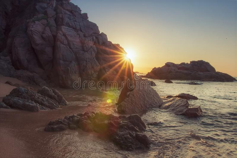 Rocky beach at sunrise with sunrays. Vivid sunbeams behind rock on sea beach. Tropical nature in morning. Paradise lagoon in spain. Rocks and stones on sandy stock images