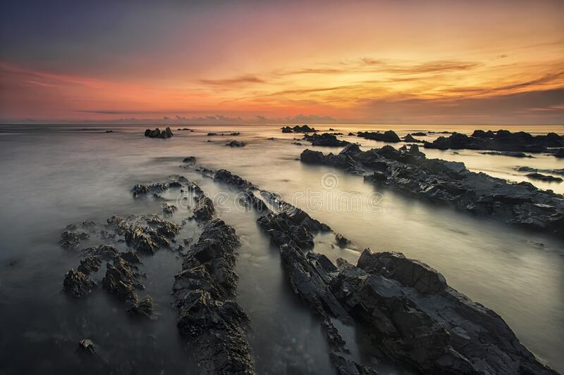 Rocky beach at sunset stock images