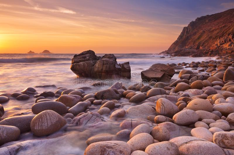 Rocky beach at sunset, Porth Nanven, Cornwall, England. The beautiful rocky beach of Porth Nanven in Cornwall, England at sunset royalty free stock photos