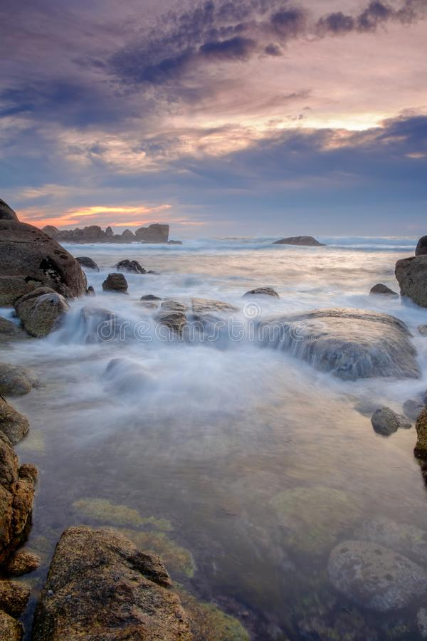 Rocky beach at sunset. With cloudy sky royalty free stock photography
