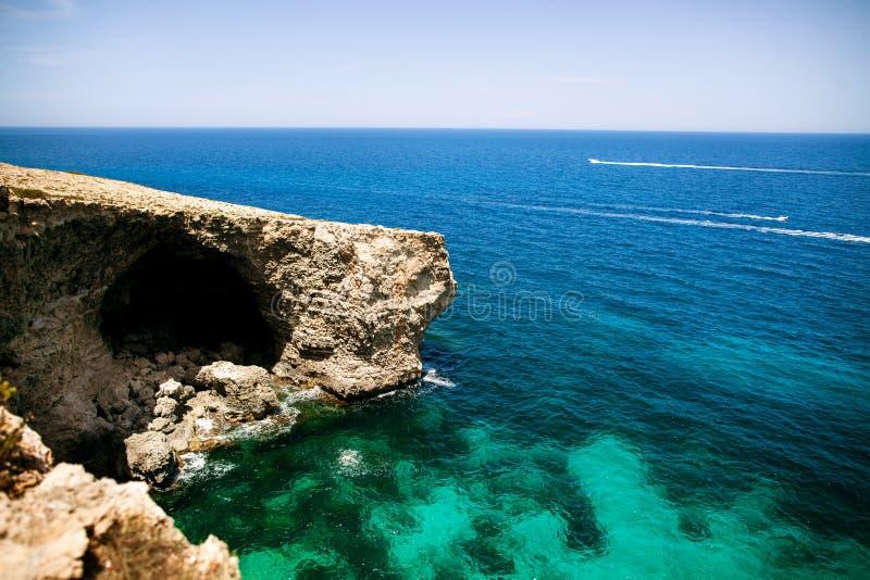 Rocky Beach y gruta con agua azul imagenes de archivo