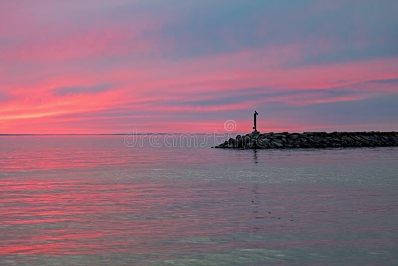Rocky Breakwater With Red Sky und Wasser lizenzfreies stockfoto