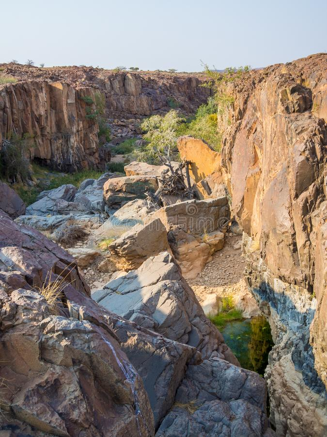 Rocky canyon with green bushes and trees in Palmwag Concession, Namibia, Southern Africa.  royalty free stock photography