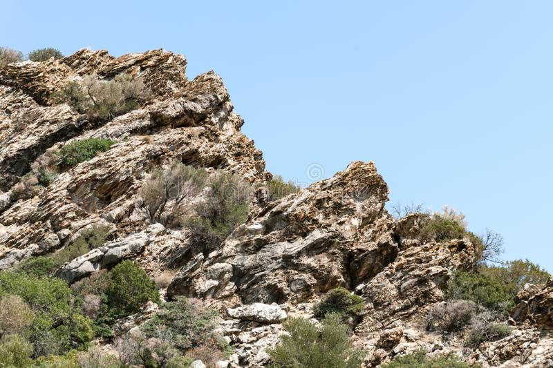 Rocky cliff against blue sky stock image