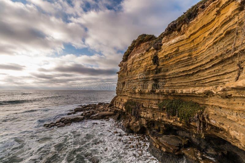 Rocky Cliff met Bewolkte Hemel en Oceaan bij Zonsondergangklippen stock foto's