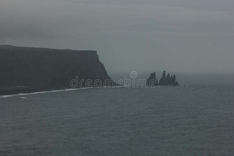 rocky cliff and ocean under cloudy sky at Dyrholaey promontory royalty free stock photography