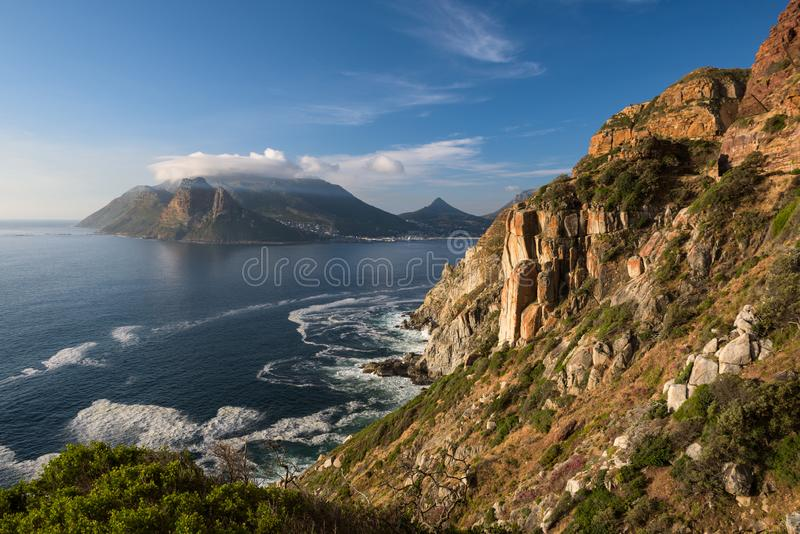Rocky cliffs on the coastline of the Atlantic Ocean near Cape Town on Chapman's Peak Drive royalty free stock images
