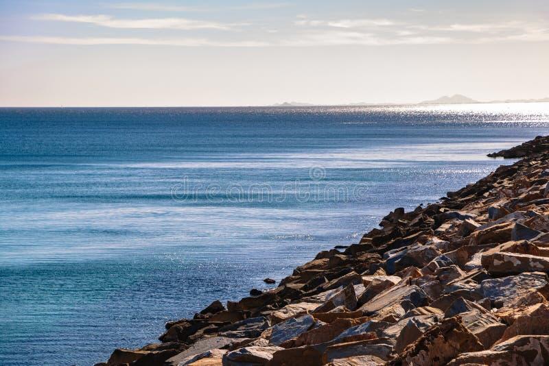 Rocky coast and calm blue sea under sky royalty free stock photos