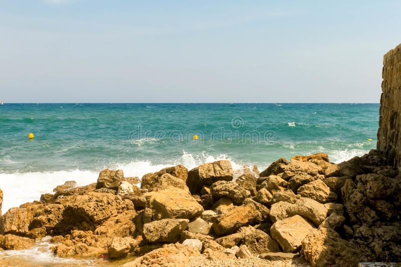 Rocky coast of the Cote d`azur sea of France Antibes near the port. French riviera stock image