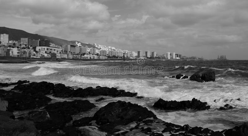 Rocky coast, Las Palmas de Gran Canaria. Rocky coast with rough sea and city in the background, Las Palmas de Gran Canaria, monochrome effect royalty free stock image