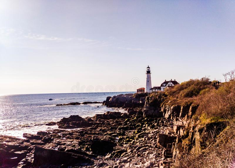 Rocky Coast of Maine with Portland headlight in the Distance stock photo