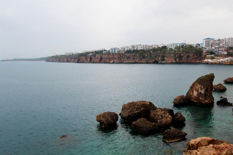 The rocky coast of the Mediterranean Sea. There are hotels on the shore. Antalya, Turkey, April 6, 2019 stock images