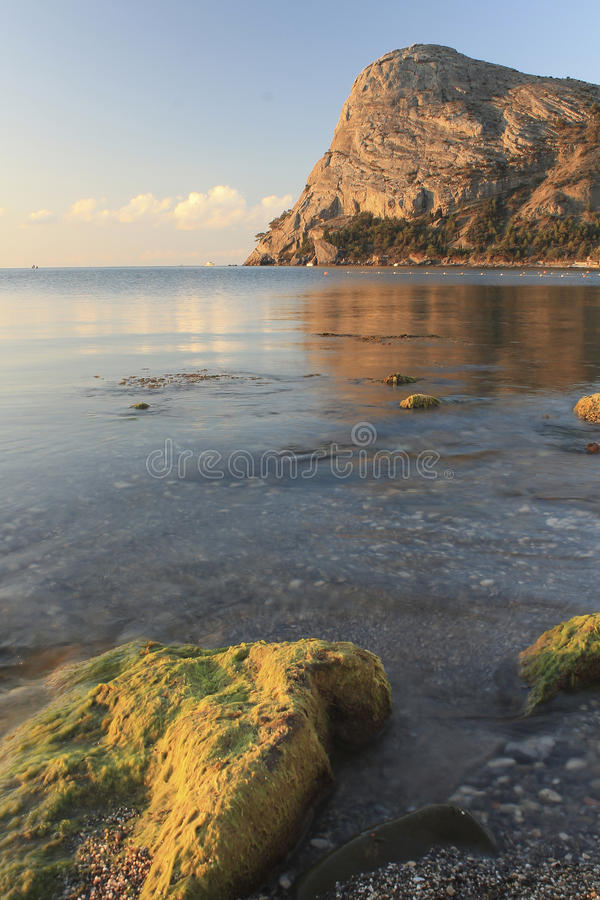 Rocky coast in the rays of the rising sun royalty free stock photo