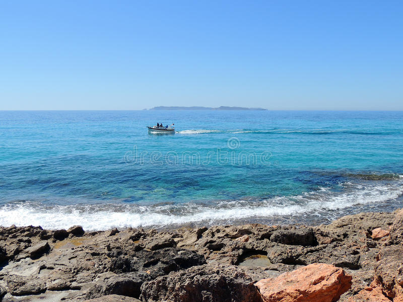 Rocky Coast rouge, bateau en mer bleue images stock
