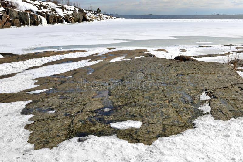 Rocky coast of snow-covered island of Helsinki archipelago, Finland stock photography