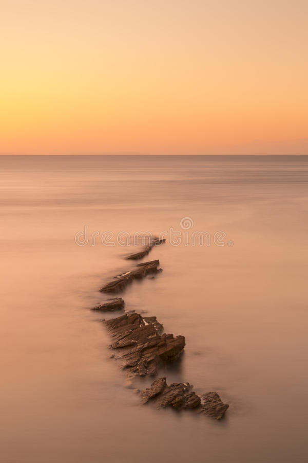 Rocky Coast Sunrise. Dawn on the Jurassic Coast in Dorset showing rocks at Peveril Point in Swanage stock images