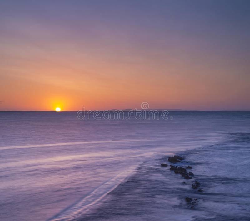Rocky Coast Sunrise. Dawn on the Jurassic Coast in Dorset showing rocks at Peveril Point in Swanage royalty free stock photography