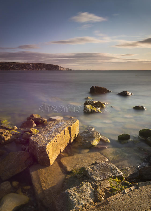 Rocky Coast Sunrise. Dawn on the Jurassic Coast in Dorset showing rocks at Peveril Point in Swanage royalty free stock photos